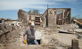 Dean Dye looks over a storm shelter in a home that was destroyed by a tornado on May 22, 2013 in Moore, Okla. (©Scott Olson/Getty Images)