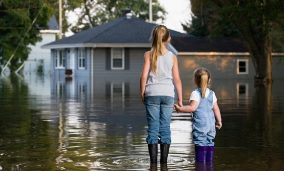 Young girls looking at flooded home (Tetra Images/Getty Images)