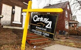 for-sale sign in front of an abandoned house in Detroit, Mich. (© Bill Pugliano/Getty Images)