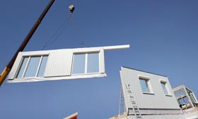 Modular home on a crane. Modular homes are speeding rebuilding efforts on the Jersey Shore. (© altrendo images/Getty Images)