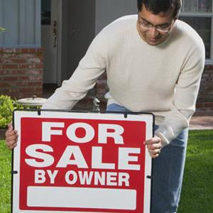 Man putting For Sale sign in lawn (© Ocean/Corbis)