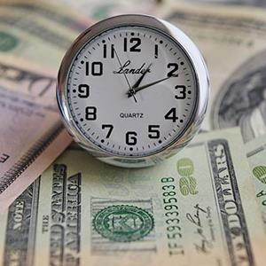 Clock sitting on pile of money (© Rafael Ben-Ari/Alamy)