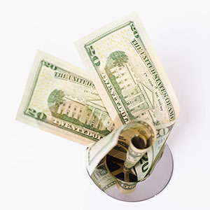 Dollars down drain © Stockbyte/SuperStock