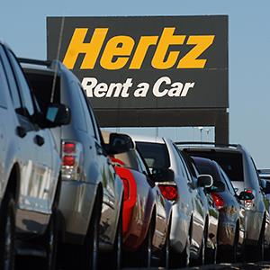 Credit: © Matthew Staver/Bloomberg via Getty ImagesCaption: A row of rental cars are parked below a sign for Hertz Corp. at Denver International Airport