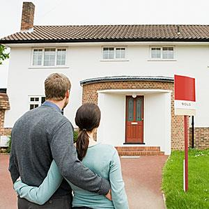 Couple outside their new house © Image Source/Getty Images
