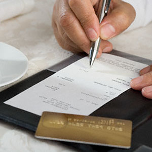 Paying a restaurant bill with a credit card © Tetra Images, Corbis