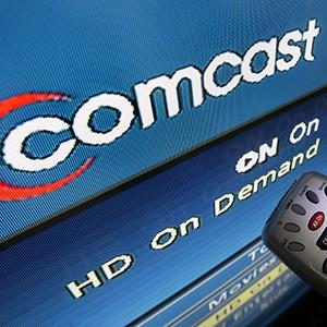 File photo of the Comcast logo on a television screen (© Elise Amendola/AP Photo)