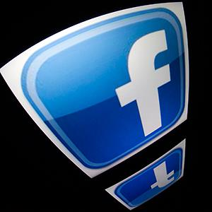 Caption: The 'Facebook' logo is seen on a tablet screen