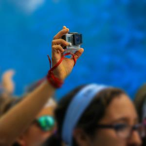Girls recording in first person with GoPro in the Color Run by Desigual. Blue color powder. © Moment Editorial/Getty Images