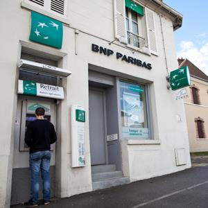 A customer uses an automated teller machine (ATM) outside a branch of BNP Paribas SA bank in Jouars-Pontchartrain, France © Balint Porneczi/Bloomberg via Getty Images