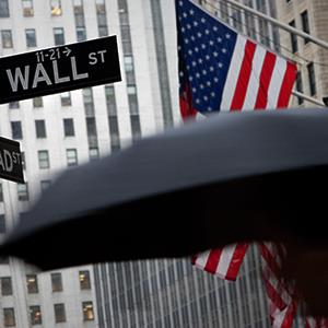 A pedestrian carrying an umbrella passes a U.S. flag on Wall Street in front of the exterior of the New York Stock Exchange in New York © Scott Eells/Bloomberg via Getty Images