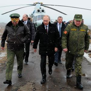 Russian President Vladimir Putin, center, and Defense Minister Sergei Shoigu, left, and the commander of the Western Military District Anatoly Sidorov, right, walk upon arrival to watch military exercise near St. Petersburg, Russia, Monday, March 3, 2014. © Mikhail Klimentyev/AP Photo