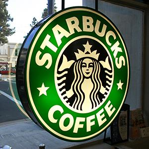 Caption: Starbucks sign hanging in the window of their coffee shop store in Seattle, Wash.