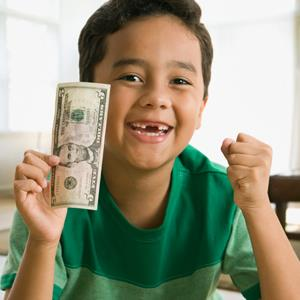 Boy holding money from the tooth fairy © Jose Luis Pelaez Inc/Blend Images/Getty Images