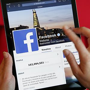A Facebook page is displayed on a computer tablet © Peter Macdiarmid/Getty Images