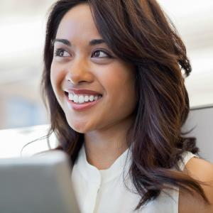 Smiling woman with digital tablet in office © Hero Images, Getty Images