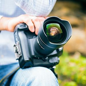 A photographer holding a big DSLR camera. © nullplus/Getty Images