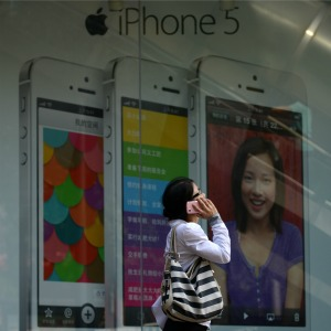 A woman uses a mobile phone as she walks past an Apple iPhone 5 poster outside a store in Beijing © WANG ZHAO/AFP/Getty Images