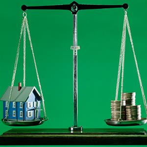 House and money balancing on scales © Comstock Images/Jupiterimages