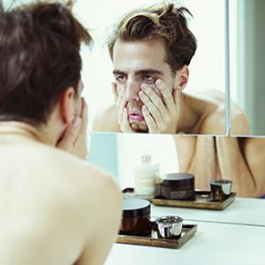 Hungover man examining himself in mirror © REX/Caiaimage