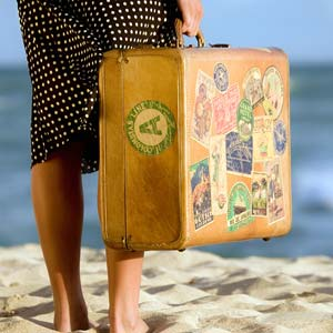 Woman holding a suitcase at the beach (© Gary S Chapman/Getty Images)