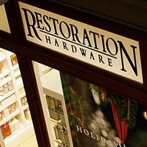 A shopper passes by the window display of a Restoration Hardware store © David Zalubowski/AP Photo