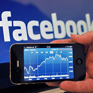 An Apple iPhone4s displaying the stock exchange app in front of a computer screen with the Facebook logo © Jan-Philipp/dpa/Corbis