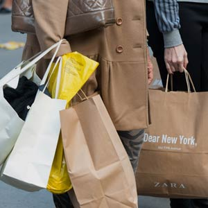 Shoppers carry bags while waiting for a taxi cab on 5th Avenue in New York. © Craig Warga/Bloomberg via Getty Images
