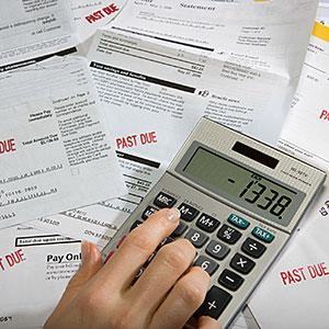 Woman using calculator on desk full of bills and statements © Sheer Photo, Inc/Photodisc/Getty Images