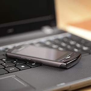 Close up of smartphone on laptop keyboard © Marek Mnich/Getty Images