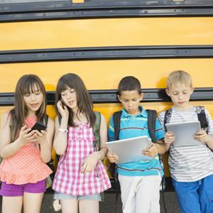 Gradeschool children at the school bus © Hero Images/Corbis