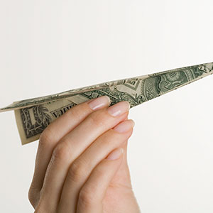 Paper airplane made of money © Tetra Images/Corbis