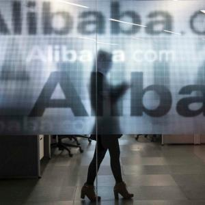 An employee is seen behind a glass wall with the logo of Alibaba at the company's headquarters on the outskirts of Hangzhou, Zhejiang province, April 23, 2014. © CHANCE CHAN/Newscom/Reuters