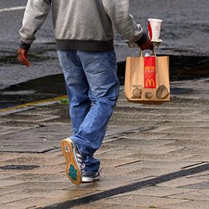 Person carrying McDonalds drink and bag of food (© format4/Alamy)