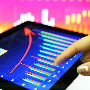 Caption: Businesswoman touching stock chart on tablet