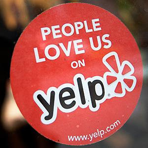 Caption: The Yelp Inc. logo is displayed in the window of a restaurant in New York