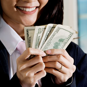 Young woman holding Money © Glowimages/Getty Images