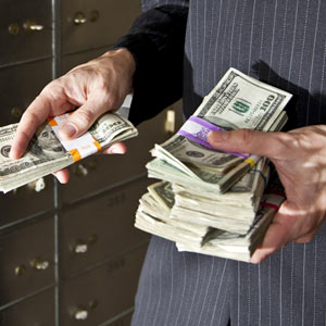 Man with cash by safety deposit boxes © kali9/Getty Images