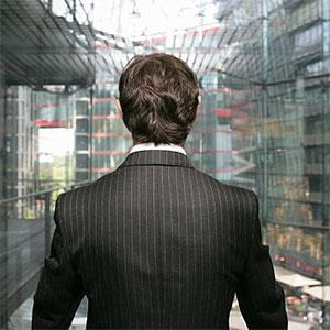A business man looking out of a glass elevator © Stella, fStop, Getty Images