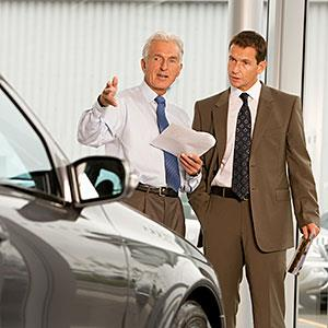 Mature salesman showing businessman car in showroom © Sam Jordash., Digital Vision, Getty Images