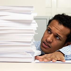 Man with paperwork (© MM Productions/Corbis/Corbis)