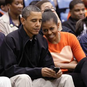 President Barack Obama uses his BlackBerry as first lady Michelle Obama talks to him at a NCAA basketball game between Oregon State Beavers and Towson Tigers at Towson University in Maryland, Nov. 26, 2011 © REUTERS/Yuri Gripas