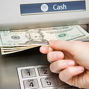 Person withdrawing cash © Image Source/Image Source/Getty Images