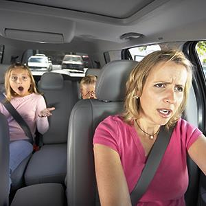 Mother driving car, two children sitting in back seat