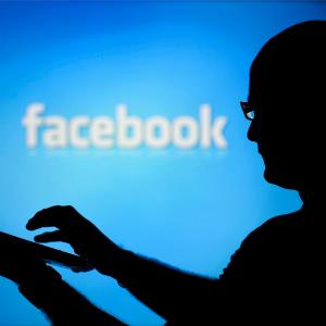 A man is silhouetted against a video screen with a Facebook logo. © REUTERS/Dado Ruvic/Files