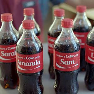 Credit: © Coca-Cola via YouTubeCaption: Still of Coca-Cola promo video showing Coke bottles with names