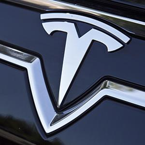 The Tesla logo, on the front of a Tesla Model S luxury electric car parked in the lot at Tesla Headquarters, Palo Alto, Calif. © REX/ZUMA