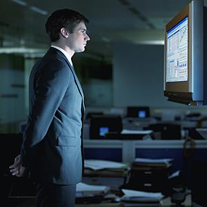 Caption: Businessman studying stocks on a monitor