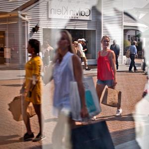 Image: File photo of shoppers reflected in a window at the Premium Outlets at Woodbury Common in Central Valley, New York (© Emile Wamsteker/Bloomberg via Getty Images)