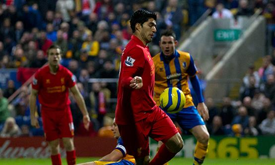 Luis Suarez handles the ball on the way to scoring against Mansfield